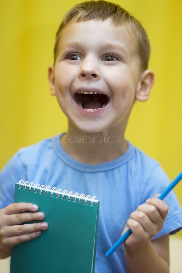 Pojken med anteckningsboken är lycklig royaltyfri foto