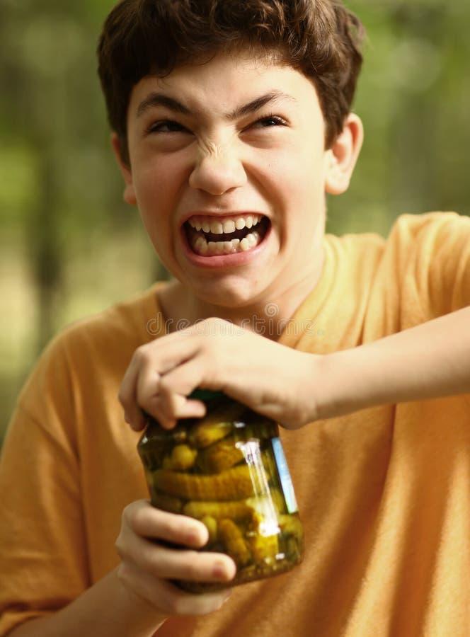 Pojken med belastningsgrimasförsök att ta bort räkningen från gurkor skorrar royaltyfri foto