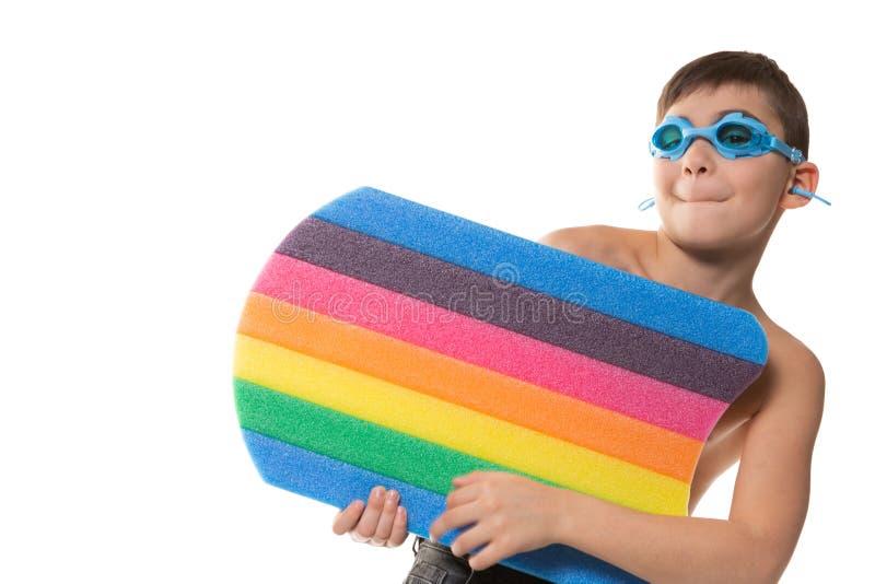 Pojken med blå simma skyddsglasögon och att ha ett badbräde som har gyckel, ansiktsuttryck och gester, vilar begrepp, på en vit arkivbild
