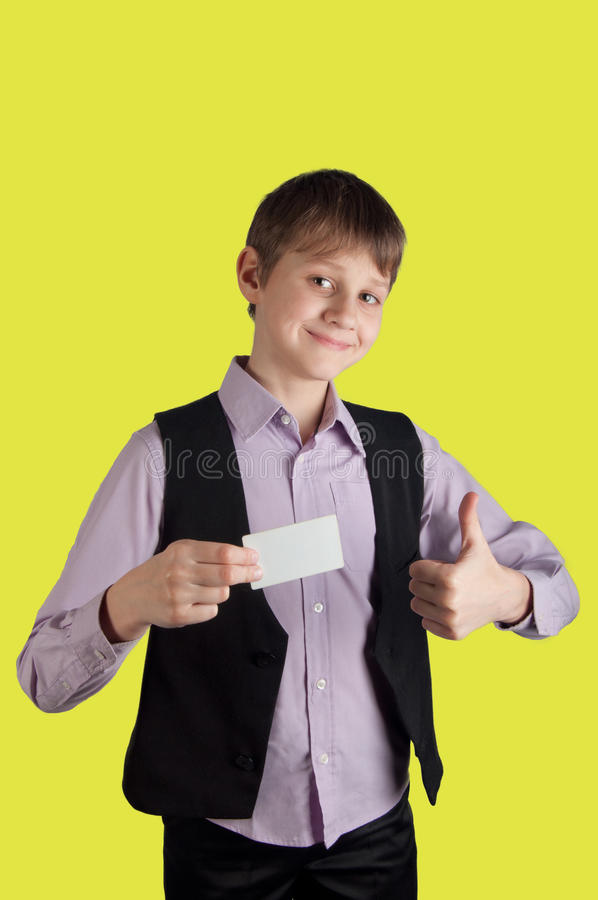 Pojken med den vita kreditkorten på gul bakgrund ler, och shower fingrar upp royaltyfri bild
