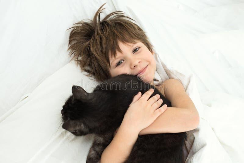 Pojken med en katt ligger i en säng på vit sängkläder royaltyfria bilder