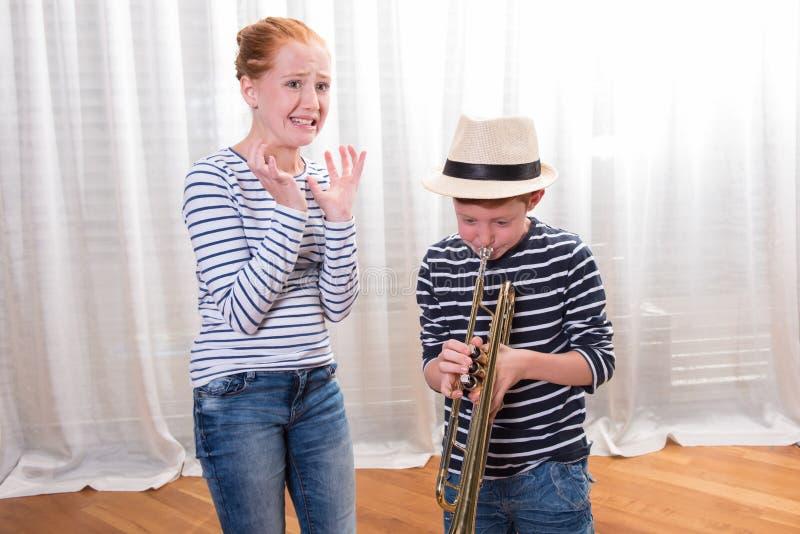 Pojken med hatten spelar trumpeten - den förargade systern royaltyfria bilder