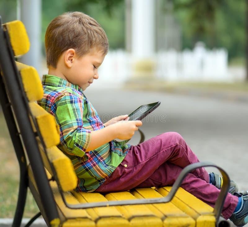 Pojken med minnestavladatoren parkerar in royaltyfria bilder