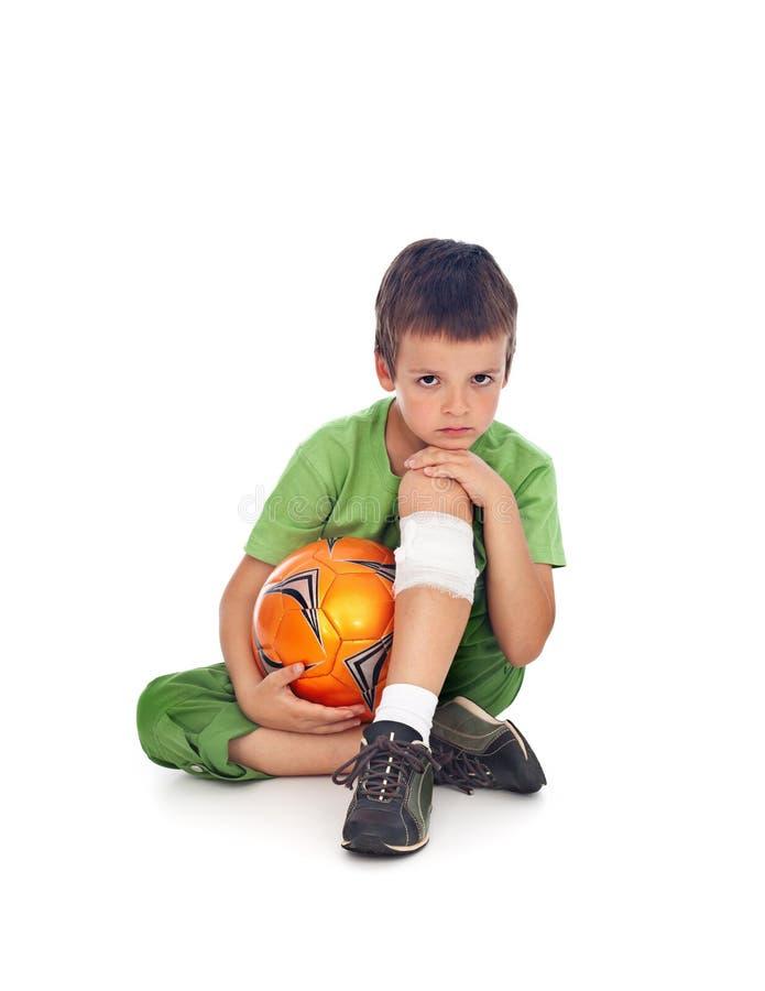 Pojken med såradt lägger benen på ryggen, och fotboll klumpa ihop sig arkivfoton