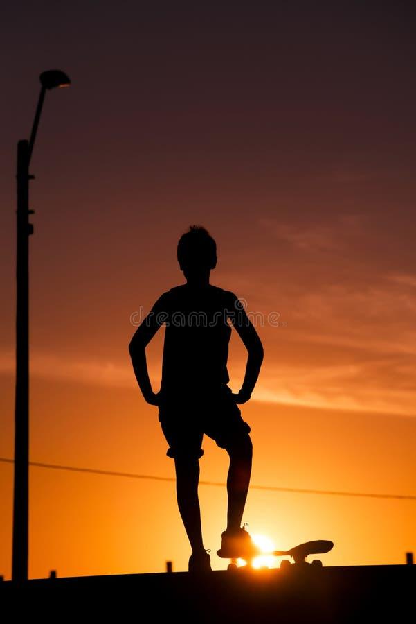 Pojken med skateboarden på skridsko parkerar rampen arkivfoton