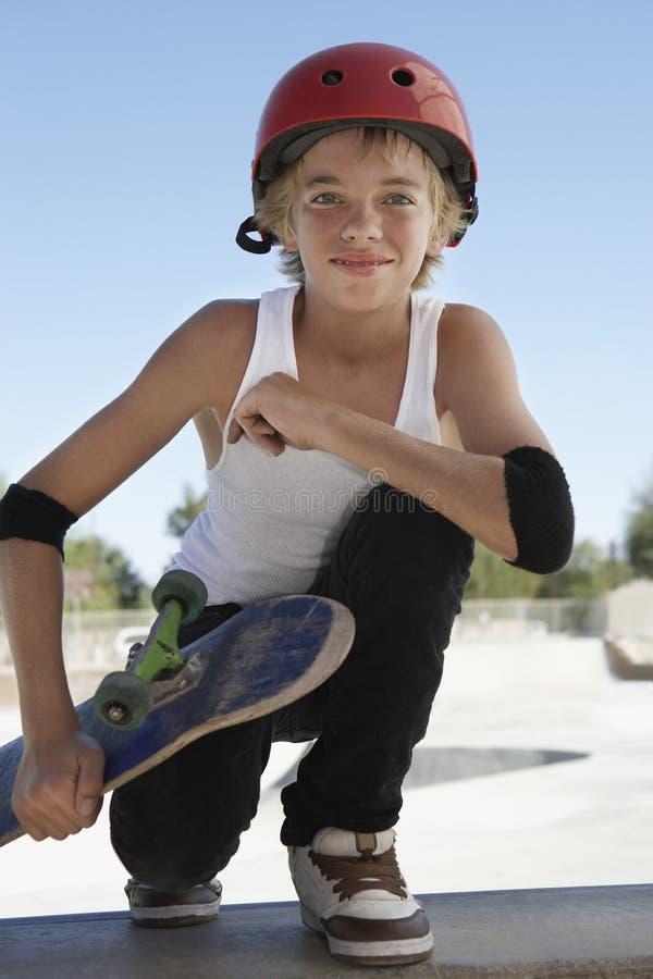 Pojken med skateboarden som Squatting i skridsko, parkerar royaltyfria bilder