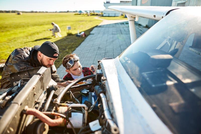 Pojken med skruvmejsel hjälper fadern att fixa den brutna motorn av det lilla flygplanet royaltyfri foto