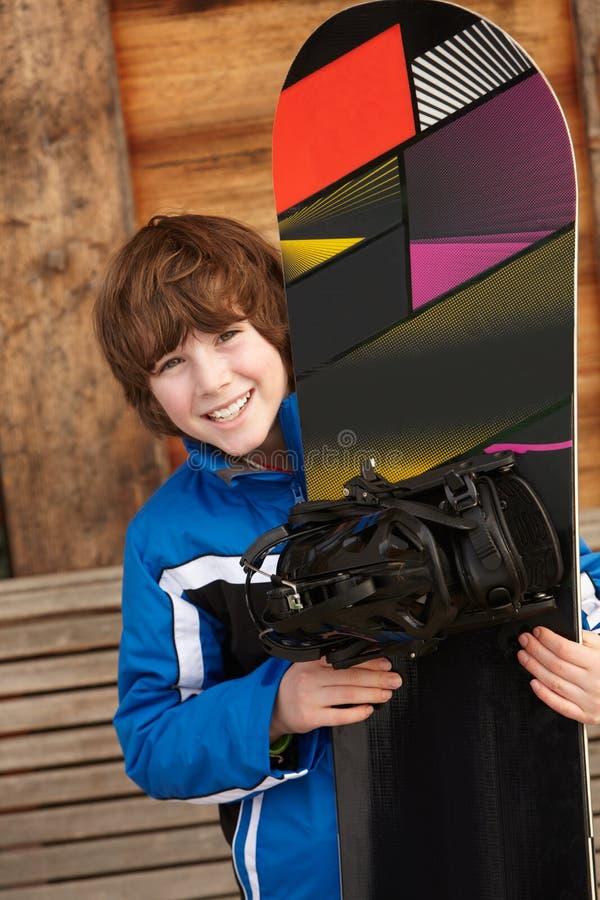 Pojken med snowboarden skidar på ferie royaltyfria bilder