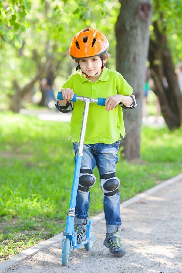 Pojken med sparksparkcykeln royaltyfri fotografi