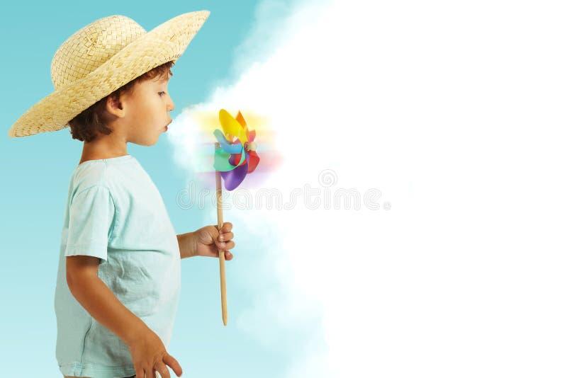 Pojken med sugrörhatten som har gyckel med wind, mal royaltyfri fotografi