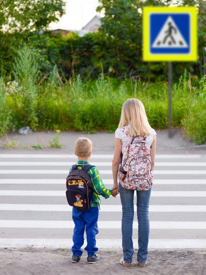 Pojken och flickan önskar att korsa vägen på en övergångsställe royaltyfria bilder