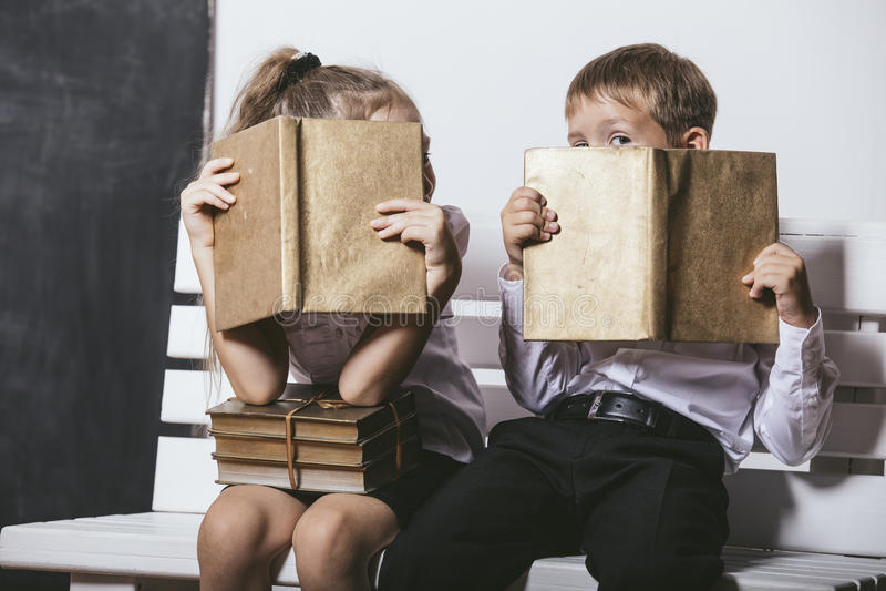 Pojken och flickan från grundskola för barn mellan 5 och 11 årgrupp på den lästa bänken bokar nolla royaltyfria foton