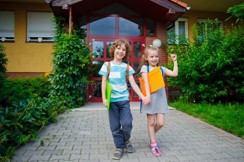 Pojken och flickan går till skolan som har sammanfogat händer royaltyfri bild