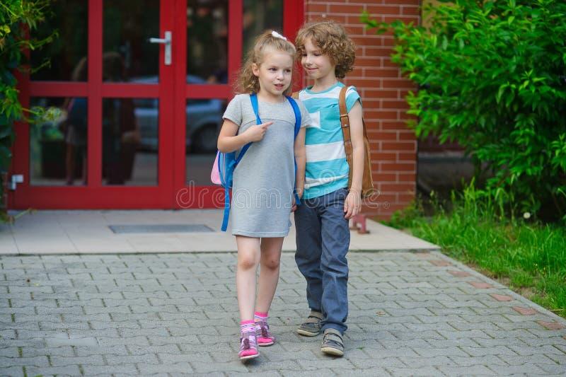 Pojken och flickan går till skolan som har sammanfogat händer arkivbilder