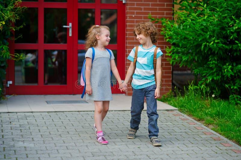 Pojken och flickan går till skolan som har sammanfogat händer royaltyfri fotografi