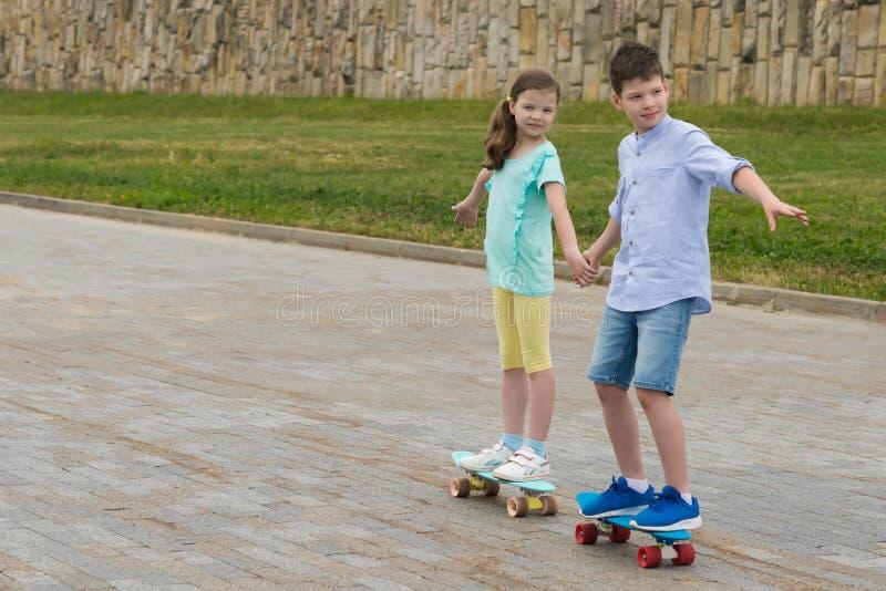Pojken och flickan har sammanfogat händer och går på skateboarder för en gå i sommaren i parkera arkivfoton