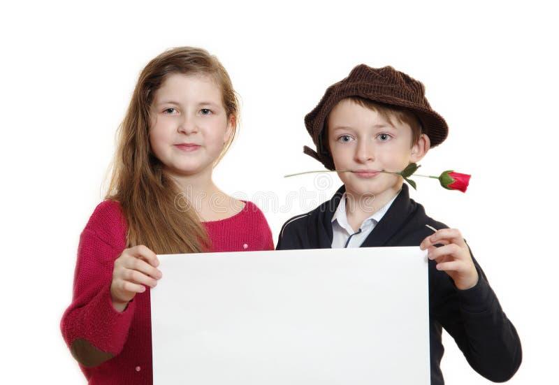 Pojken och flickan med ett vitt ark arkivfoto