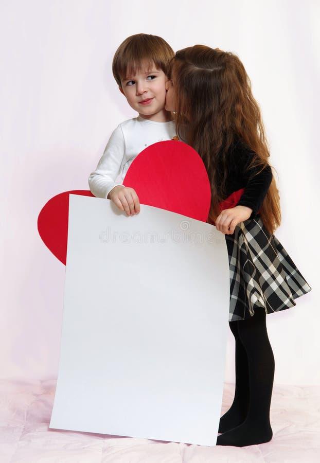 Pojken och flickan med ett vitt ark arkivfoton