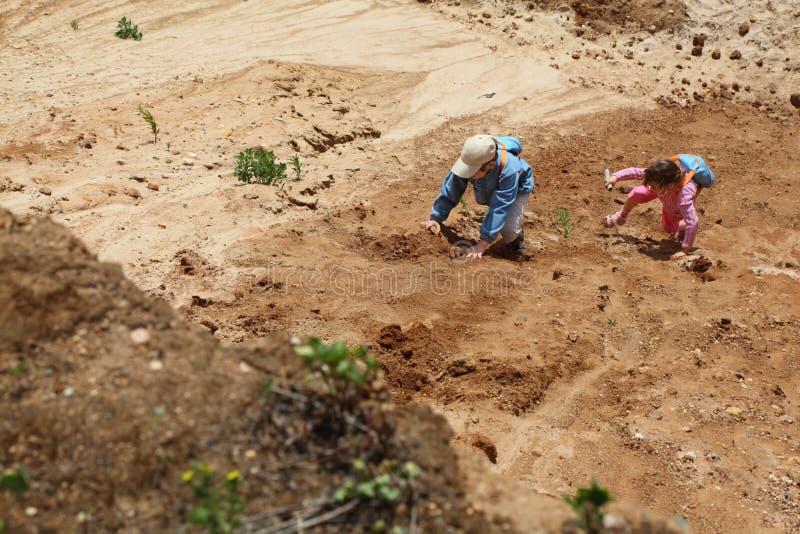 Pojken och flickan med ryggsäckar clamber på sanden. royaltyfria bilder
