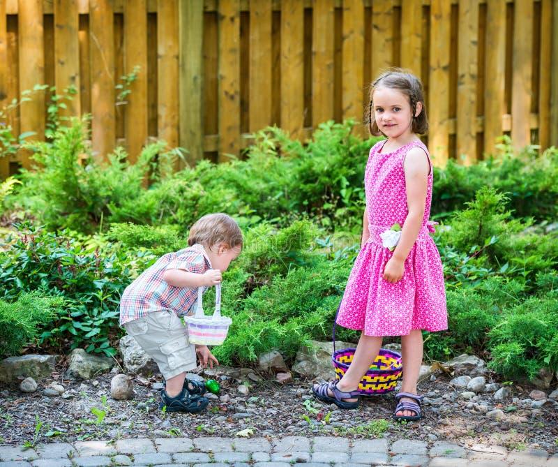 Pojken och flickan söker efter påskägg royaltyfri foto