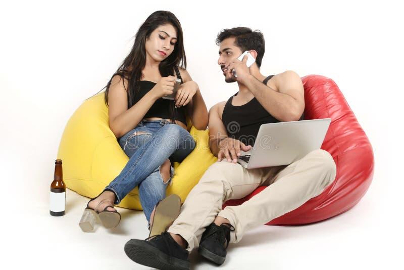 Pojken och flickan sitter med bärbara datorn och flaskan Pojken som talar på, ringer royaltyfria foton