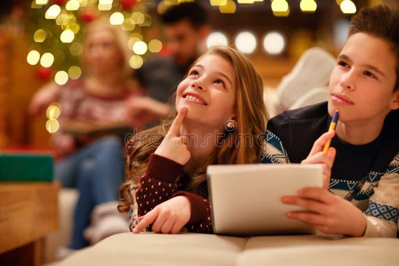 Pojken och flickan som ligger och, skrivar brevet till Santa Claus för Christma arkivbild