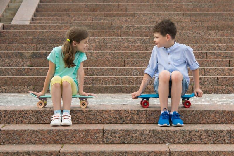 pojken och flickan sorterar saker ut och att sitta på momenten på sportbrädena arkivbilder