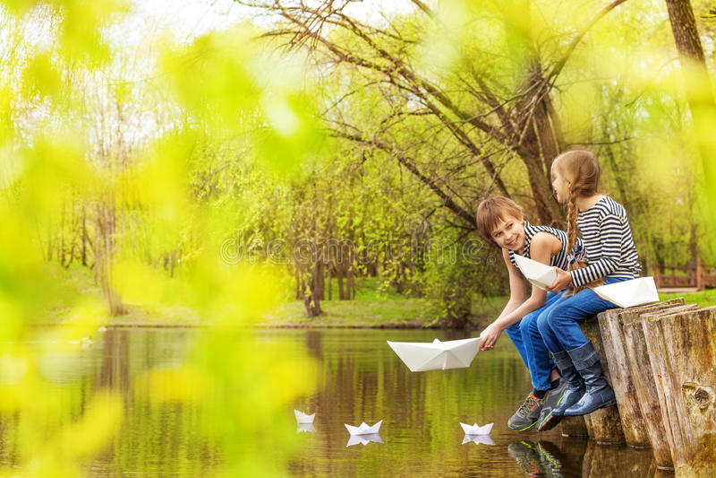 Pojken och flickan spelar med pappers- fartyg på flodvatten royaltyfri bild
