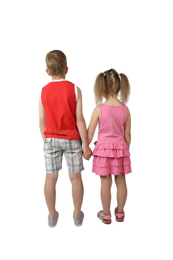 Pojken och flickan står rymma tillbaka händer arkivfoto