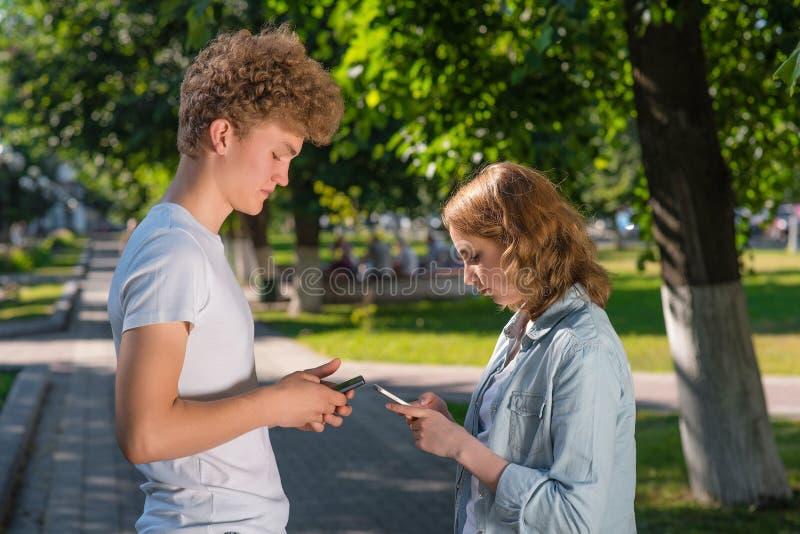 Pojken och flickan vänder mot sig Sommar i natur I hans händer rymmer en smartphone Skriver telefonnumret royaltyfri fotografi