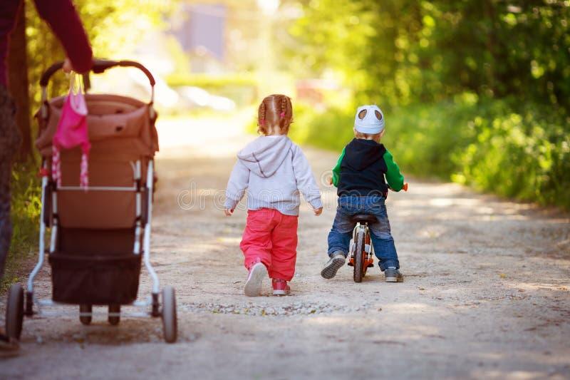 Pojken och pojken som går i skogen i sommar med modern och en jämvikt, cyklar royaltyfri fotografi