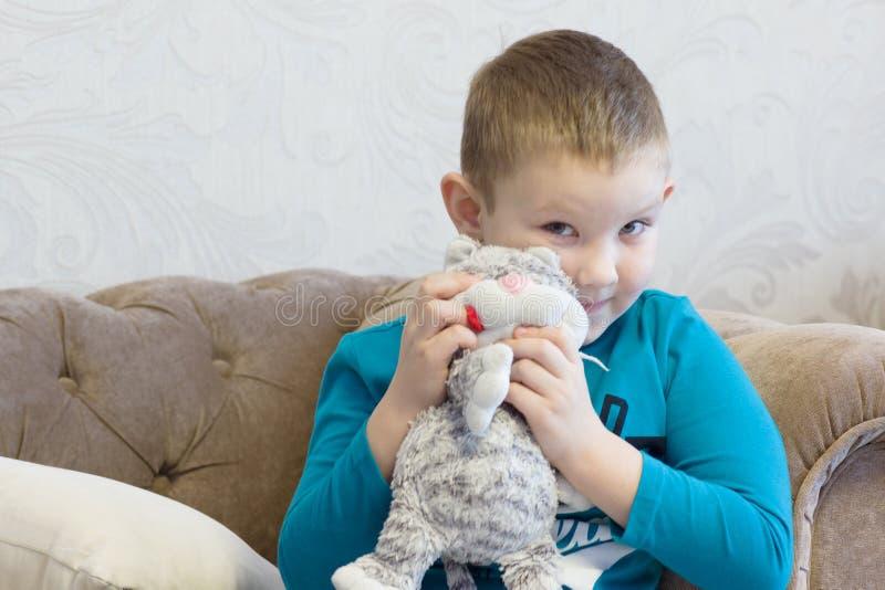 Pojken omfamnar den flotta leksaken arkivfoto