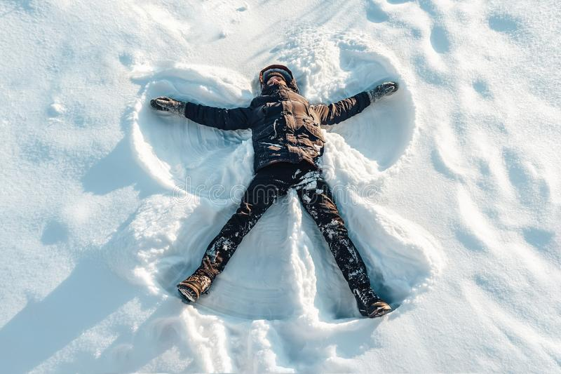Pojken på en snöslående beväpnar och lägger benen på ryggen ängelshower arkivfoton