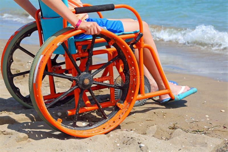 Pojken på en special hjulstol observerar havet från stranden arkivfoton