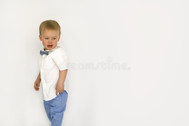 Pojken på en vit bakgrund gråter arkivfoton