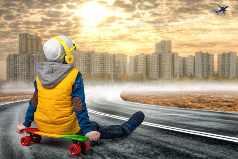 Pojken på skateboarden, blickar på nivån i himlen Pysen i stilen av Hip Hop Den unga rapparen Kyla rap dj arkivbild