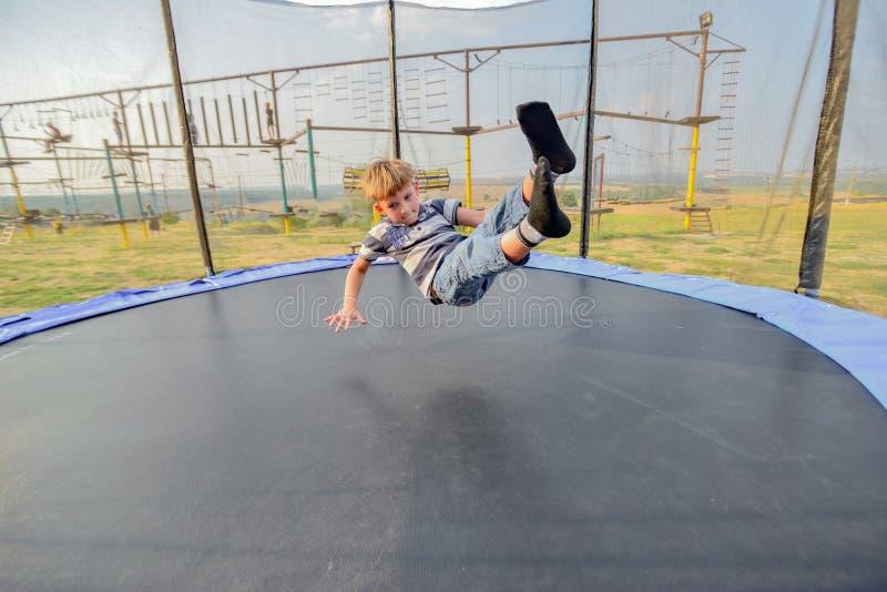 Pojken på trampolinhoppen till överkanten med hans fot, brett vinkelfoto royaltyfri fotografi