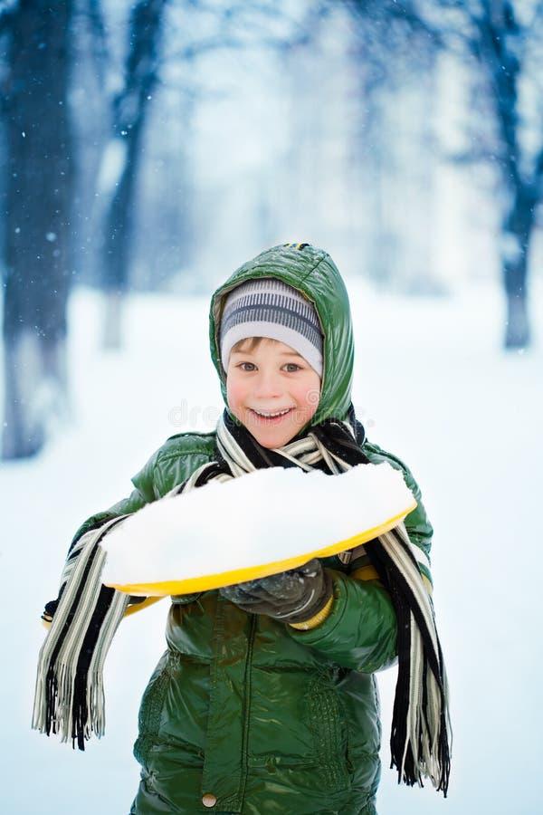 Pojken plaing med snow på naturen. fotografering för bildbyråer