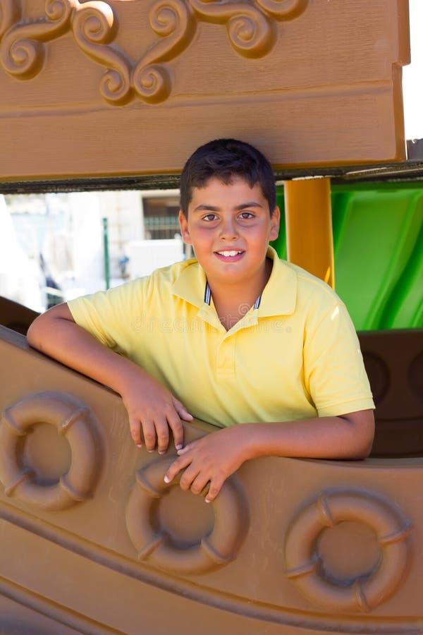 Pojken poserar till kameran i lekplatsen royaltyfria bilder