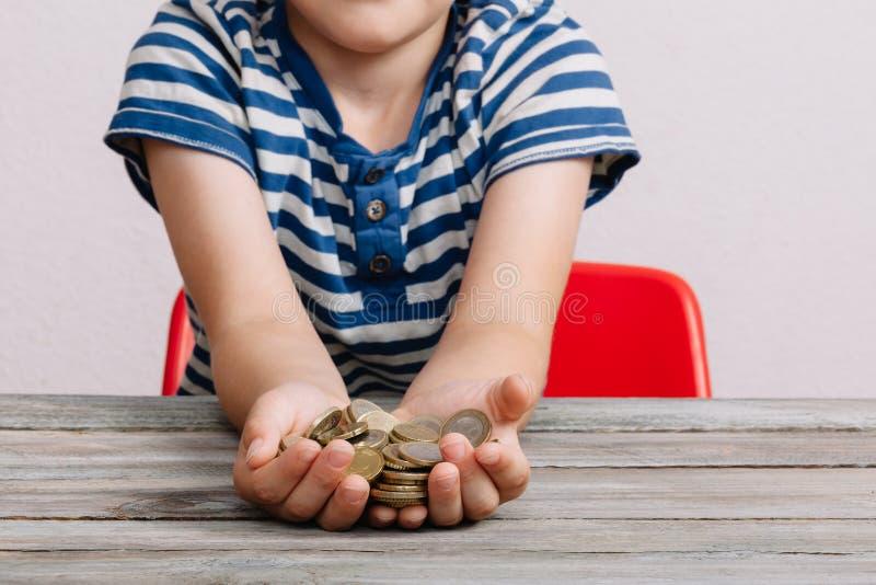 Pojken räcker hållande pengarmynt arkivfoton
