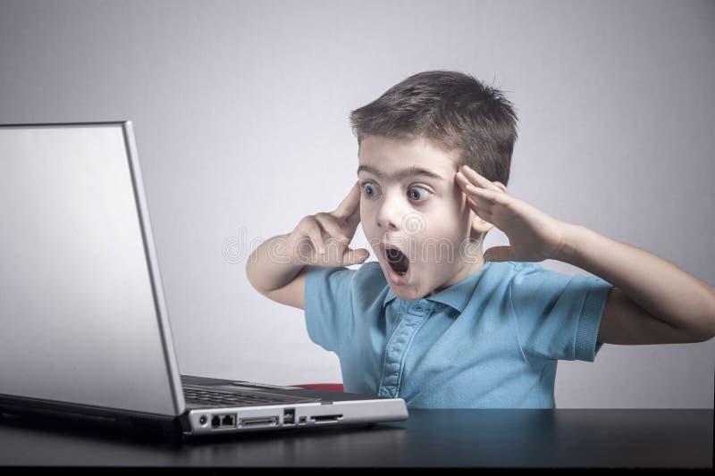 Pojken reagerar, medan genom att använda en bärbar dator arkivfoton