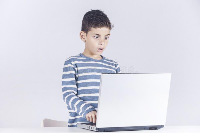 Pojken reagerar, medan genom att använda en bärbar dator arkivbild