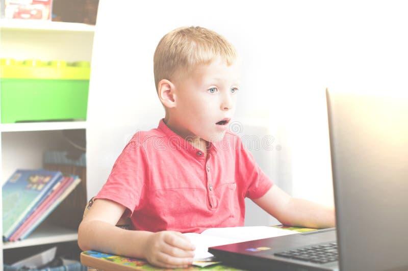 Pojken reagerar, medan genom att använda en bärbar dator royaltyfri foto