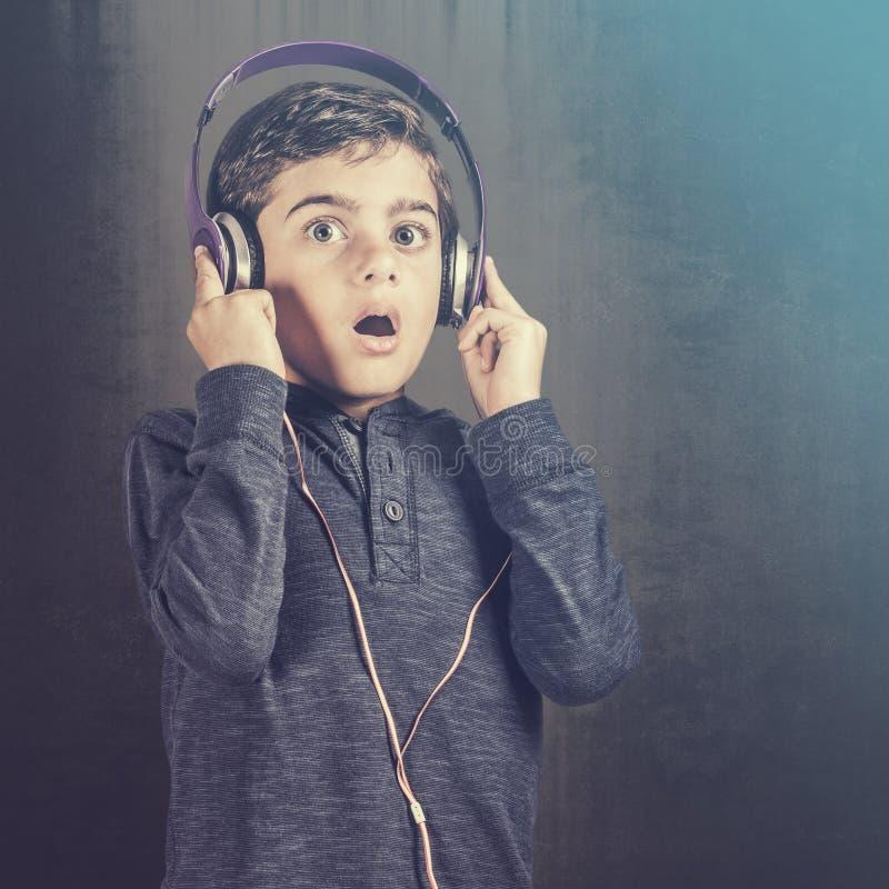 Pojken reagerar, medan lyssna till musik royaltyfri bild