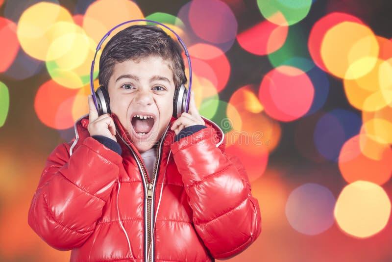 Pojken reagerar, medan lyssna till musik arkivfoto