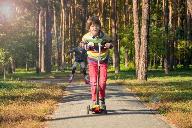 Pojken rider en sparkcykel som följs av en flicka med råttsvansar på arkivbilder