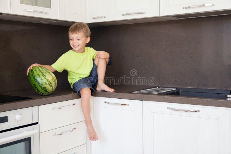 Pojken rymmer en stor grön vattenmelon royaltyfri bild