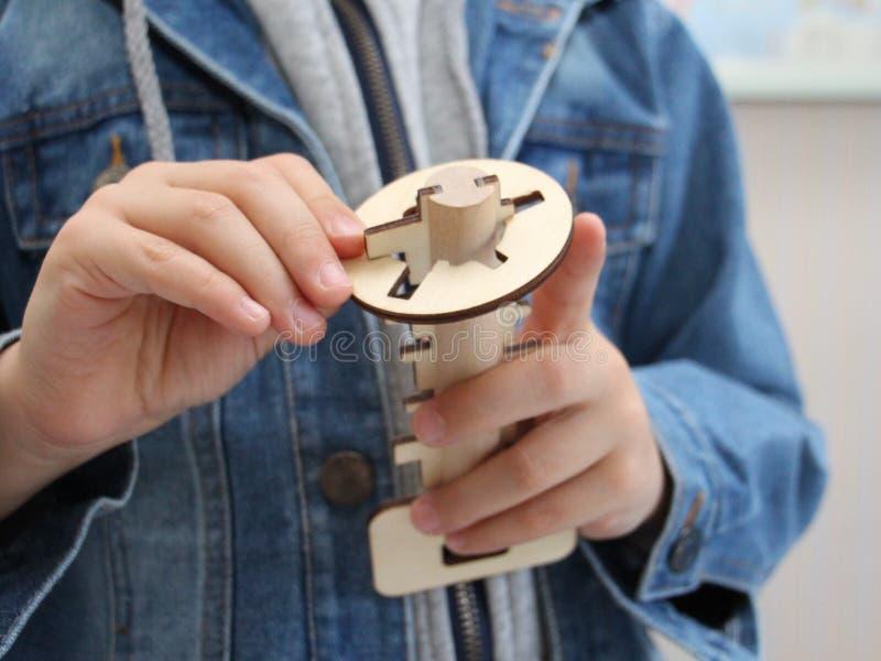Pojken rymmer en träleksak i hans hand Trätangent och nyckelhål fotografering för bildbyråer