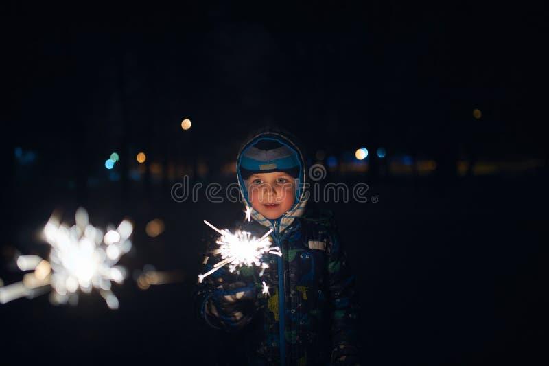 Pojken rymmer ett tomtebloss i hans händer, medan fira ett nytt år på gatan på natten arkivbild
