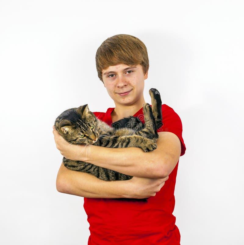 Pojken rymmer hans strimmig kattkatt i hans armar royaltyfri bild